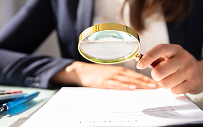 photo closeup of person holding a magnifying glass over a piece of paper, portrays analysis and review