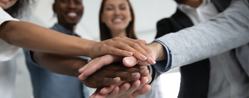 Close up photo of a group of people and their hands stacked on top of each other. Symbolizes strength, team, unity, diversity